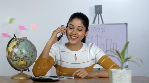 Portrait of a modern smart Indian girl talking and smiling on the phone - Office setup