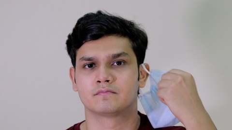 Closeup of an Indian guy takes off his surgical mask against the white background
