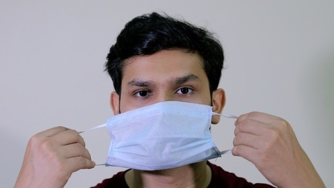 Closeup shot of a young boy using a medical mask during the Covid-19 pandemic