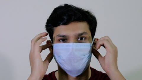 A young attractive boy removes his protective medical mask to breathe fresh air