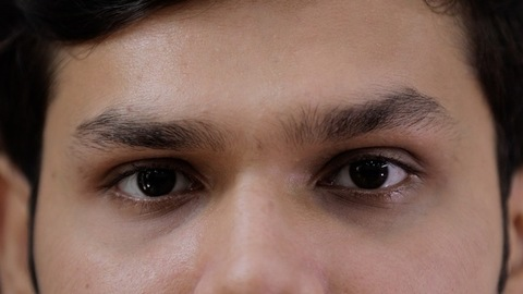 Extreme close up of a young teenager's black eyes looking towards the camera