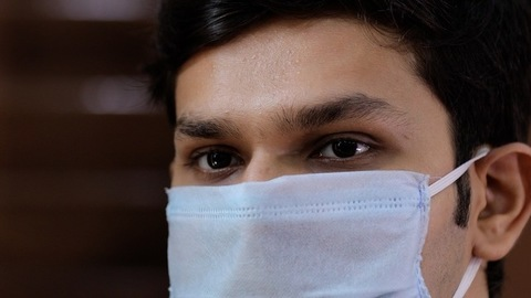 Extreme close up of an Indian guy wearing a surgical mask to avoid coronavirus outbreak