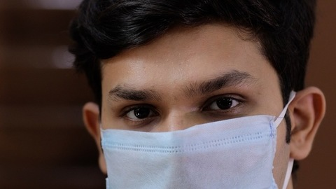 Portrait of a young serious boy in protective face mask to prevent Covid-19 pandemic