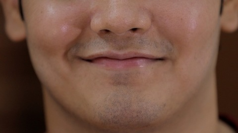 Extreme portrait close up of an Indian guy's face smiling - happy emotions