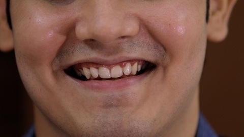 Extreme portrait close up of an Indian guy's face laughing - happy emotions