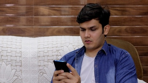 A cute teenage boy getting happy after receiving a text on his mobile phone