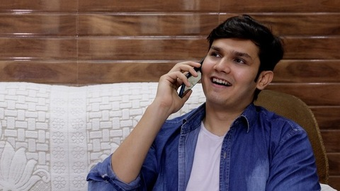 Handsome Indian college boy happily talking to his best friend over a phone call
