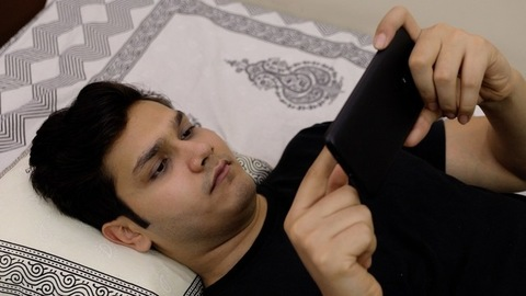 High angle shot - Young attractive teenager watching videos on his smartphone