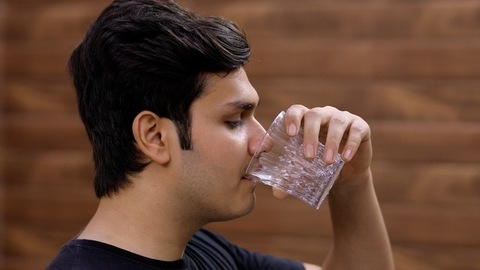 Closeup shot of a handsome Indian teenager drinking a glass full of freshwater