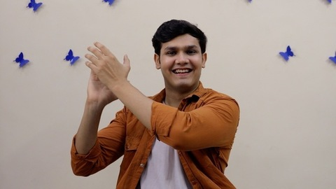 A young attractive guy happily clapping hands while looking towards the camera
