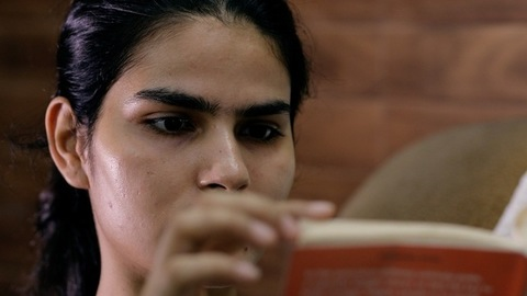 Extreme close up of an attractive Indian female reading a book - leisure time