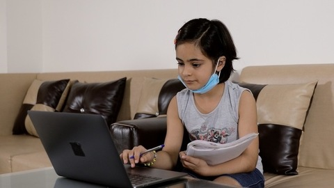 Cute Indian girl learning at home on her laptop while wearing a medical mask