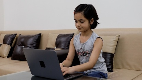 Cute little Indian girl using her laptop while sitting on a couch - casual clothing