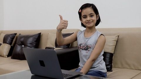 Portrait of a cute little girl sitting comfortably on a couch and showing a thumbs-up sign