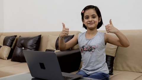 Adorable Indian kid happily gesturing double thumbs-ups while using her laptop