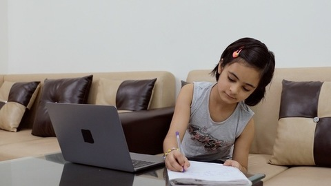 Attractive Indian kid/child sincerely learning new things on her laptop - lifestyle kids