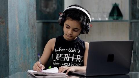 A cute little girl in black headphones taking online school classes on her laptop