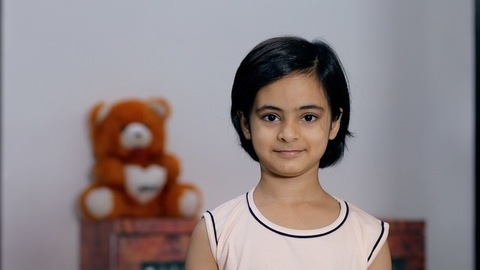 Medium shot of a cute little girl smiling while looking at the camera - casual wear