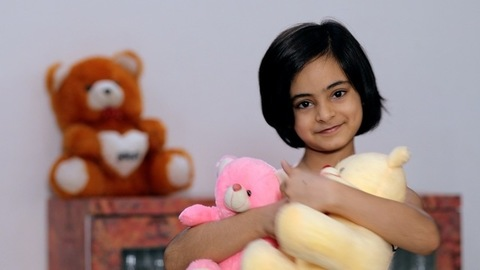 Cute little girl smiling while holding teddy bears in her arms - kids lifestyle concept