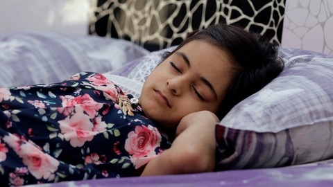 Closeup shot of an adorable Indian girl sleeping comfortably in her bedroom