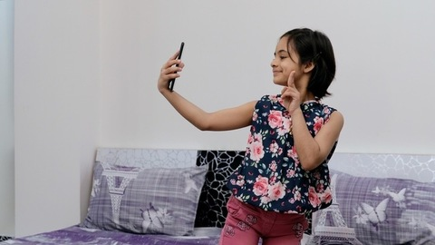 Cute little girl taking selfies in different poses with her smartphone - leisure time