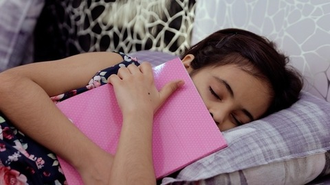 Pan shot - Cute little girl sleeping in her bed while hugging her favorite storybook