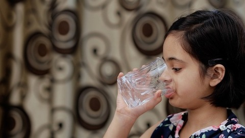 Closeup shot of a beautiful Indian girl drinking a glass full of fresh water at home