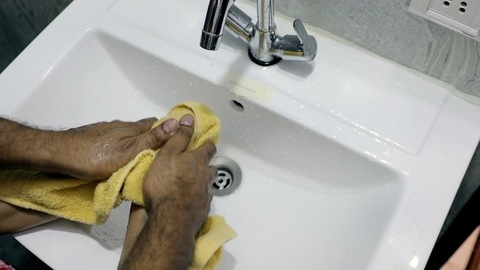 Closeup of hands of an Indian father helps to wash his little daughter's hands