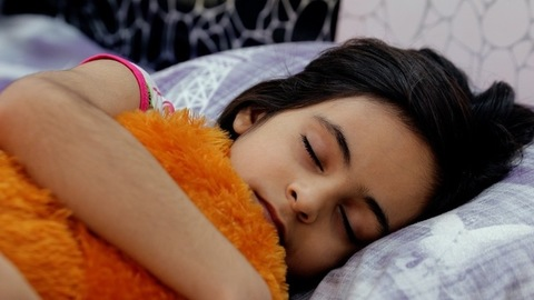 Pan shot of a cute little girl sleeping in her bed while hugging her favorite soft toy