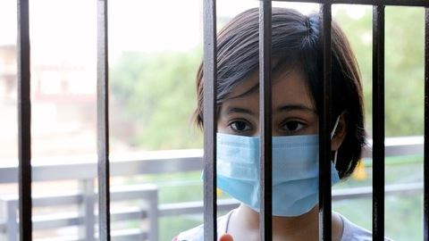 Portrait of a bored Indian kid in a medical mask looks outside during the home quarantine