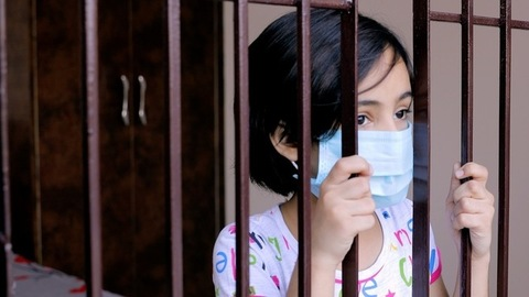 Closeup of a young girl looking through the window while wearing a surgical mask