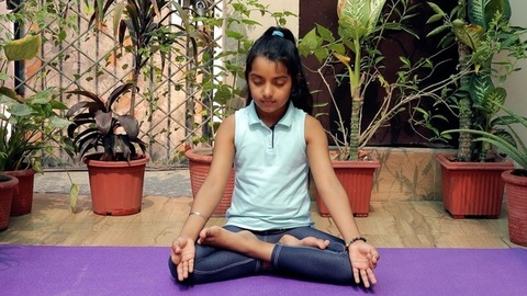 Cute little kid/child doing breathing exercises with closed eyes in lotus pose