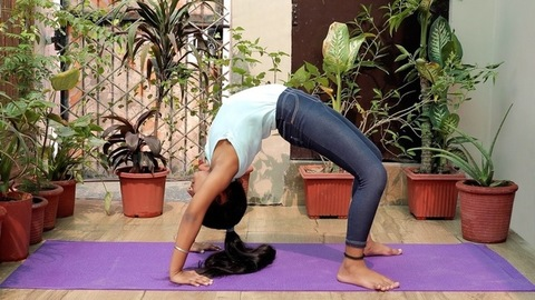 Flexible Indian girl doing Urdhva Dhanurasana (wheel pose) on a fitness mat