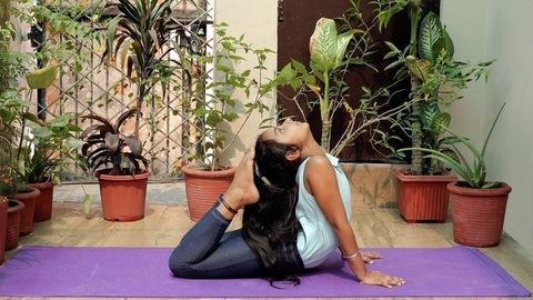 A medium shot of a cute little girl doing Raja Bhujanagasana on a fitness mat
