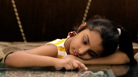Closeup shot of a cute little girl leaned against a table - boring lifestyle concept