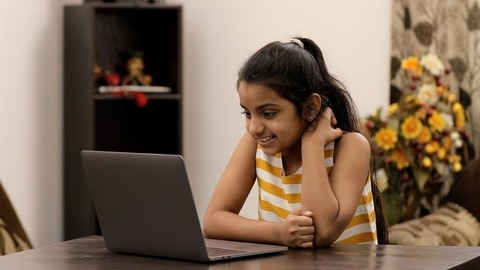 Medium shot of a cute little girl happily talking on a group video call via laptop
