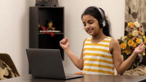 Medium shot - Cute little girl showing dance moves to her friends on a video call