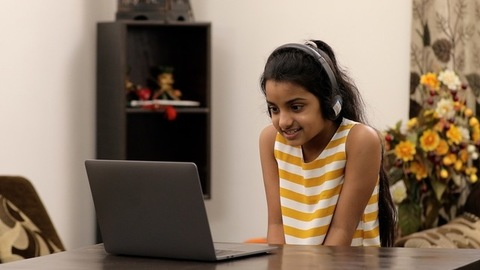 Young innocent kid busy doing a video call from her laptop - modern technology