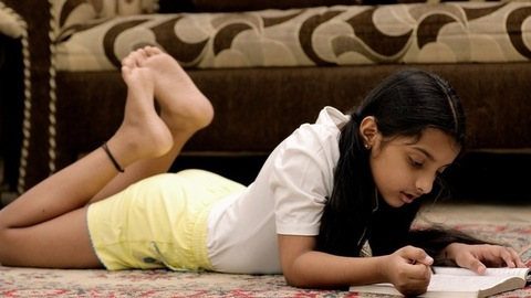 Young sincere schoolgirl reading her storybook at home - childhood education