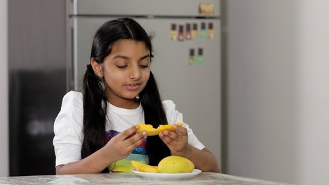 Medium shot - Cute young girl enjoying a slice of mango while sitting on a table