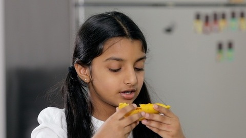 Closeup shot of a pretty young child adorably eating a slice of mango at home