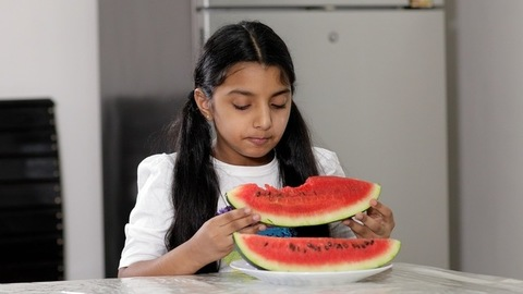Cute little girl happily eating the slices of a yummy watermelon at the dining table