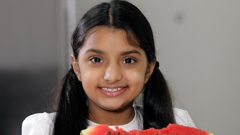 Closeup shot of a cute little girl happily eating a slice of watermelon at home