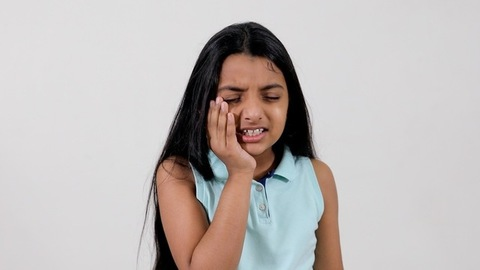 An upset little girl suffering from a severe toothache against the white background