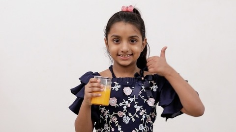Medium shot - Cute little girl gesturing thumbs-up after drinking mango juice