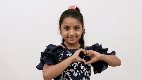 Medium shot of a cute little girl smiling and making a heart shape with her hands