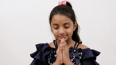 Medium closeup shot of a cute little kid smiling while worshiping God - faith concept