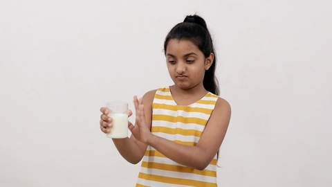 Medium shot of a little girl denying a glass of milk due to stomach fullness