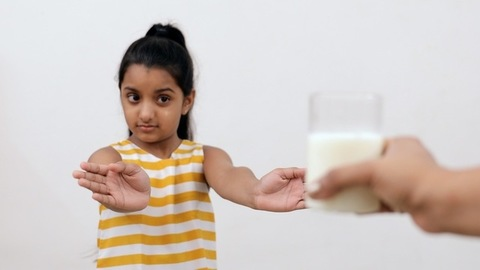 Medium shot of a young Indian kid saying no to the milk given by her mother