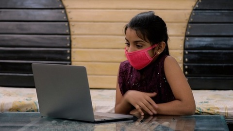 Medium shot of a pretty Indian girl doing a video call while wearing a medical mask